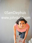 Picture of a woman climbing a lader taken from above. The camera is looking straight down at this stock photo of a black woman climbing a lader. Pink blouse and big smile.
