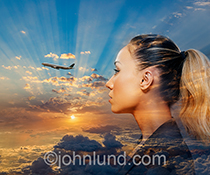 A Woman is contemplating travel, her head superimposed over a brilliant sunrise with a distant aircraft ascending towards an unnamed destination in a stock photo about travel, journeys and other concepts.