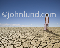 An African American woman in a pink dress wears a gas mask and stands on a vast expanse of dry, cracked barren wasteland.