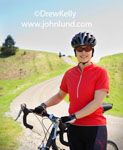 Close up portrait of a Chinese American woman in cylcing gear standing with her bicycle on a country gravel road surrounded by green grass covered hills.  Happy smiling women with bikes. Picture of an asian woman smiling at the camera.