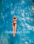 Beautiful fit healthy woman in a black two piece swim suit makes a beautiful dive into deep blue water. Spa or resort advertising photo.