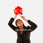 Stock photo of an attractive young woman using a kitchen knife to get money out of a piggy bank. She is holding the bright red piggybank over her head using a table knife to get the coins out of the bank. Need money?