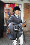 Picture of a woman carrying an English riding saddle. She is wearing her equestrian riding gear. Pictures of horse women.