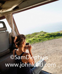 Picture of a woman sitting in her van drinking a cup of coffee. She is sitting cross legged and is viewed from behind.  Grassy hill and ocean in the background.  Woman wearing tank top and drinking coffee in a camper van.