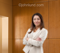 A woman executive stands in a corporate business environment pixelated and digitized in a stock photo about women and business in the digital age.