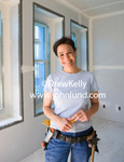 Happy middle-aged woman wearing a carpenters tool belt and smiling at the camera. The woman is standing in a room of a newly built home not quite finished.  The room has just been sheetrocked.  Picture of woman carpenter or construction worker.