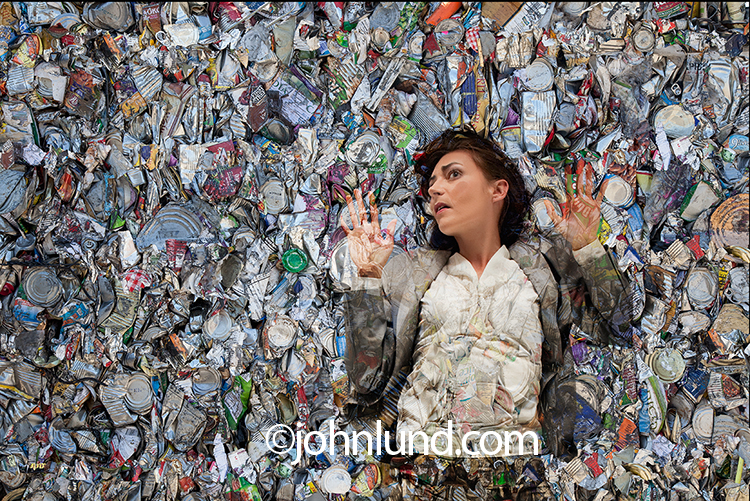 In this environmental photo a woman has been compacted in a bale of aluminum in an image about ecological issues, recycling, and intelligent uses of resources.