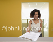 Picture of a woman holding out a clip board, in an office setting, with a form, job application or medical paperwork either filled out or needing to be filled in.