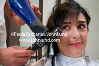 Photo of a woman having her hair styled in a beauty salon or beauty shop. Woman in a hairdresser's shop having her hair done by a professional hair stylist. Beauty shop pics.