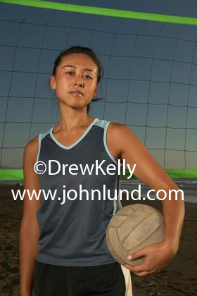 Photo of a young woman athlete holdikng a volleyball under her arm in front of a volleyball net on the beach. She has a serious look on her face. Asian or Chinese ethnicity. Pics of hot looking women athletes for advertising.