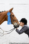Picture of a woman kissing a horse. The woman, an equestrian, has on her English riding gear including a riding helmet and she is holding the horses jaw and kissing him on the nose. The horse is wearing a blue ribbon.