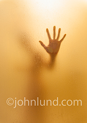 A woman, her hand pressed against the frosted glass wall, is seen, out of focus, in a wet and steamy shower in a stock photo about everything from health and beauty to issues of depression and loneliness.
