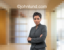 A woman executive stands in a virtual office in this stock photo in which the background is pixelated.