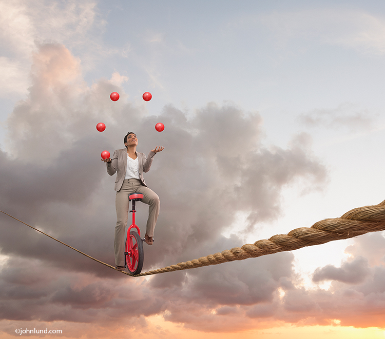 "A woman successfully rides a unicycle on a tightrope while juggling in this metaphorical photo about multitasking and the myriad of ""things"" that all of us constantly struggle with on our ""To Do"" lists."