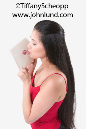 Picture of a woman kissing an envelope leaving a bright red lipstick impression on the envelope. The yound adult Mexican woman has waist long black hair and a bright red blouse.
