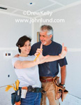 Husband and Wife Construction Team.  Picture of an older man with a toolbelt and a middle aged woman also with a toolbelt standing in a freshly sheetrocked room. Pictures for advertisiments. New home construction photos.
