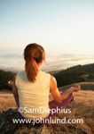 Stock photo of a senior woman sitting on a grassy hill meditating. The Asian meditating woman has a scenic view  looking down towards a valley shrouded in fog. Woman viewed from behind.