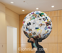 A woman, overloaded with paperwork, is seen in this stock photo holding up on her shoulders, like a woman Atlas, a giant sphere of papers, photos and records.