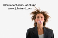 Scary looking woman with a bubble gum bubble poped on her face. Her hair is a mess... a real bad hair day. Funny picture of a businesswoman with a popped chewing gum bubble stuck to her mouth. Funny pictures.