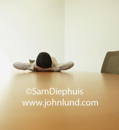 Funny stock image of a woman laying on her back on the top of the conference room table at the office. She is resting the back of her head on her hands with the top of her head pointed at the camera.