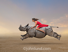 A woman in a red dress rides a galloping rhino across a vast empty plain in a dramatic image and stock photo illustrating freedom, daring, the unexpected and strong women.