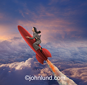 A woman rides a red rocket to success in this stock photo showing the businesswoman astride a red rocket that leaves a trail of smoke and fire as it climbs up above the clouds.