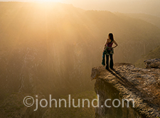 A woman stands at the top of a cliff and looks out over a gorge during a beautiful, golden sunset. She holda a climbing rope in one hand and is wearing climbing gear.
