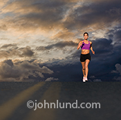 A woman runner is lit by the sun as she crests a hill in the road with dark storm clouds in the background. This is a dramatic image that highlights the driving spirit of long distance runners.