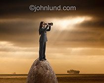 This simple, yet complex, image shows a woman in a business suit searching the horizon with binoculars while in the background a container ship approaches from across the ocean.