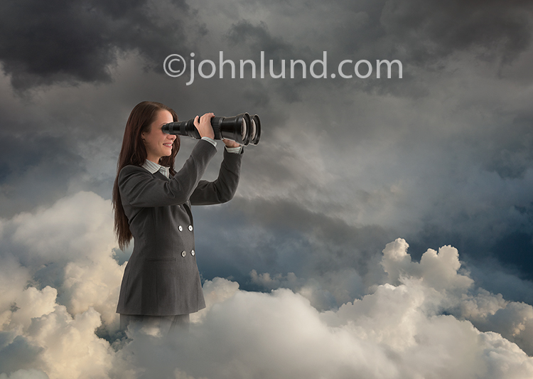 A woman stands in a cloudscape searching the cloud with huge binoculars in a stock photo about Internet searching and search engine technology and development.