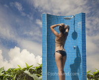 A woman, wearing a bikini, showers at an outdoor pool shower at a tropical vacation resort in this spa picture.