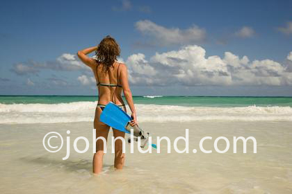 Woman walking out into the ocean with her snorkle gear. Beautiful green ocean. Womans back to camera. Shoulder length brown hair. Blue sky with clouds. Beautiful ocean scene.