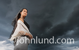 A woman stands contemplating the distance as dark storm clouds roll in behind her in an image about change.