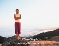 A Japanese woman wearing purple pants qand a white tank top is standing on a rock overlooking the pacific ocean. The middle aged Japanese woman has her arms folded in front of her.
