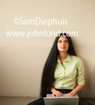 Beautiful Latina woman with long dark hair down to her waist with a laptop in her lap is gazing upward deep in thought. Beautiful women and their laptops. Woman is wearing a light green blouse. Long gorgeous hair.