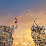 A woman, standing on the edge of a cliff, tosses a life line to a businessman standing on an opposite cliff in a stock photo about teamwork, cooperation, and assistance.