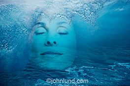A beautiful woman's face is seen beneath a breaking ocean wave in a stock photo about health, beauty and imagination.