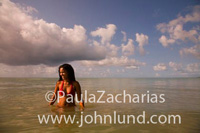 Lovely Asian or Hispanic woman standing in the ocean up to her waist in the water. She is wearing a bright red two piece swim suit. Hot ethnic woman in the ocean. Blue but cloudy sky.  Ethnic women in tropical settings.