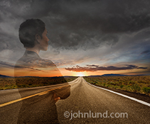 An African American woman executive is seen in a semi transparent mode over a road that stretches out from under dark storm clouds to a distant sunrise in a stock photo about possibilities, success, and the future.