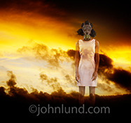 A woman stands in a smokey, toxic environment, wearing a gas mask, in a stock photo about toxic environments be they physical, mental, or emotional, in the home, workplace or public venues.