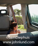 Stock photo of a woman sitting in her camper van drinking coffee on her road trip camping adventure.  Gray interior with curtains.