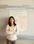 Picture of an Asian woman standing in front of a white board with business notes with her arms crossed in front of her. White sweater and shoulder length hair.