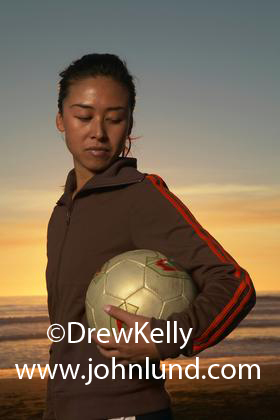 Beautiful picture of a Chinese or Asian woman holding a volley ball under her arm and looking down. She has her hair pulled back. Her background is a beautiful golden sunset over the ocean. Beach volleyball pics.