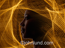 A woman is surrounded and encased in a complex and intricate web of golden light in an image about the world wide web, future communications technology and connection.