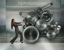 A woman pushes with all her might turning a huge gear complex in an image about determination, perseverance and making business work.