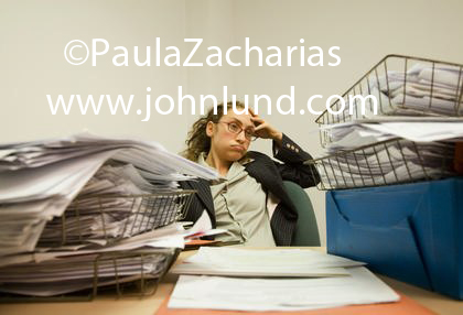 Office worker overwhelmed with paperwork. Her desk is covered with inboxes overflowing with paper and documents.  She has her hand on her forehead and lookes frustrated and despairing.