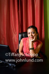 A very pretty hispanic woman is sitting at a desk in front of her laptop computer. She is wearing a pink dress and resting her chin on the palm of one hand while she looks at the camera. Sexy hispanic woman pic.