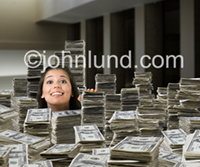 A woman is up to her neck in stacks of money, a huge pile of dollars, cash, currency and moola in a picture of success and wealth.