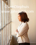 Black businesswoman standing in front of a large window with her arms crossed in front of her and staring out the window while she thinks hard about something. Business people pictures. Proffesional women photos for advertising.
