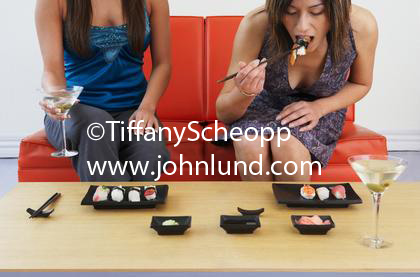 Two Asian women eating sushi and drinking martinis. One woman is holding her martini and the other woman is taking a bit of sushi. It is almost to her mouth. She is leaning forward to eat a bite of sushi.